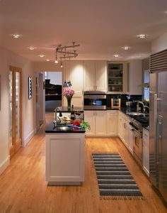 Small Kitchen Designs with Amazing Furniture Arrangements: Recessed Lighting And Pendant Lighting With White Shaker Kitchen Cabinets Also Black Countertops And Kitchen Island With Sink For Small Kitchen Designs Plus Oak Flooring #blackkitchens #furniturearrangement #kitchenislands