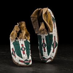 Cheyenne Beaded Hide Moccasins sinew-sewn thick hide coated in yellow pigment; beaded in translucent green, pink, red white-heart, and white; split and angled cuffs, length 11 in. fourth quarter 19th century Condition: Heel seam split on both; some repair work to heel; scattered bead loss. Price Realized Including Buyer's Premium $600 04/08/2016