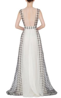 A dissonant color palette entered designer Allessandro Dell'Acqua's eccentric femme vocabulary this season, tempered by charming prints and elegant fabrics. This ** Rochas** dress exudes feminine allure in black and white gingham, with an open mesh back and gathered whie tulle detailing.