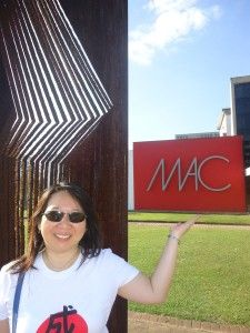 """O Museu de Arte Contemporânea, o MAC, um dos mais importantes museus de arte moderna e contemporânea da América Latina. Seu acervo possui mais de 10.000 peças, entre pinturas, esculturas, fotografias e peças conceituais de artistas como Picasso, Matisse, Miró, Kandinsky e Modigliani, entre outros. Atrás de mim, a escultura """"Perfis"""", de Simon Benetton."""