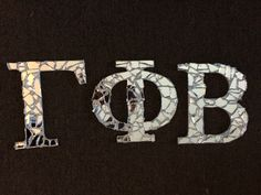 Broken glass letters I made for my little. I painted wooden letters with a metallic silver paint. Then I broke a cheap mirror from the thrift store and used mosaic glue to glue the mirror pieces to wooden letters.