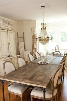 farmhouse table and French chairs. Nice juxtaposition... Table is rustic, chairs are elegant but have a sort of a rustic finish...it works together. They look like restoration hardware chairs actually...