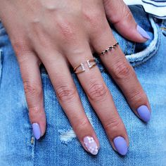 Brides.com: . A pastel blue manicure with white flowers and clear nail polish on the ring finger.