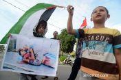 Sejumlah anak membawa gambar korban penyerangan Israel terhadap warga Palestina saat aksi Peduli Gaza di Palu, Sulawesi Tengah, Sabtu (12/7)...