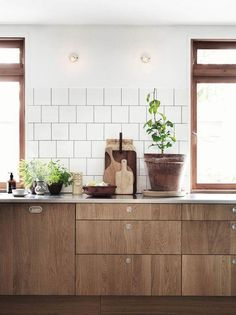 Scandinavian kitchen, with square white tiles on gray grout, unfinished, raw wood cabinets, warm wood window trim, gray and white carrara marble counter tops, recessed modern drawer pulls, mixed wood cutting boards and potted indoor plants.