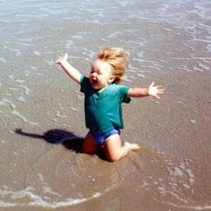 2004 Happy child at water's edge on beach, on knees in sand with arms spread wide.
