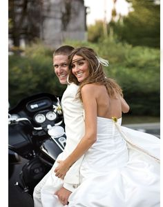 The newlyweds ride off together on a motorcycle