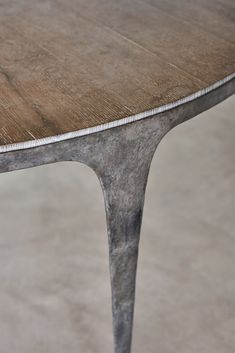 OCHRE whippet round table: Blue whippet base with a silver patination on solid cast bronze and with patinated bronze tips. The top is made by fumed and limed waxed character oak.