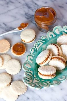 ALFAJORES (DULCE DE LECHE SHORTBREAD COOKIES) + VIDEO  Alfajores are very popular in Argentina, Uruguay, Ecuador, Chile, Paraguay, Peru, and Brazil. How had I never heard of them before? I will never know, but ever since then I've been in love with them. They are basically shortbread cookies that sandwich dulce de leche. They look very fancy but actually are very simple to make.  These cookies are beautiful for a spring brunch, a baby shower, or a wedding. They are so elegant looking.
