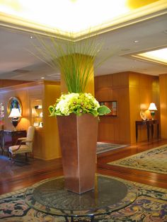 Tall modern flower arrangement of grasses, cymbidium orchids, hydrangea, and hosta leaves for a hotel lobby.
