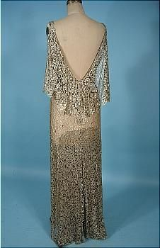 "1930s Gold Metallic Lace Evening Gown with ""v"" neck front and extremely low ""v"" neck back with flouncy shawl collar. Skirt has 6 attached scallop flyaway panels for fullness sewn to one side. Self fabric belt with rhinestone buckle."