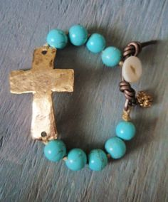 Hand knotted howlite stones flank a hammered gold pewter cross. Metallic leather loop closure with an antique mother of pearl button.
