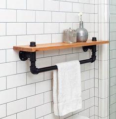Toallero de estilo industrial fabricado con tubería externa y repisa de madera en baño alicatado en azulejos blancos