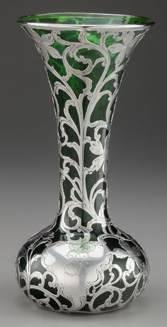 ALVIN SILVER OVERLAY GLASS VASE, Providence, Rhode Island, circa 1900 Marks: A, 925/1000 FINE, PATENTED,The green glass vase with a flared lip rim above the tapering neck leading to a bulbous base with chased silver floral and scrolling foliate overlay, cartouche to front monogrammed CC.