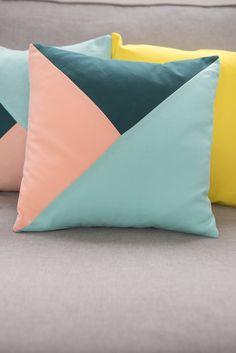 Kissen im angesagten geometrischen Look in Pastellfarben wie Türkis und Apricot als Deko für die Couch im Frühling für ein Wohnzimmer im skandinavischen vintage Look