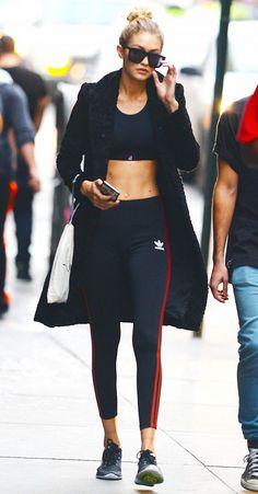 Gigi Hadid wears a sports bra, black coat, Adidas track pants, Nike sneakers, and rectangular sunglasses: