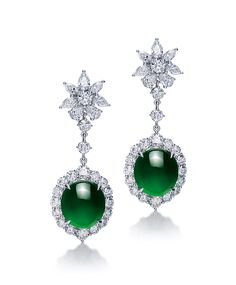 A PAIR OF JADEITE AND DIAMOND EAR PENDANTS   Each set with an oval jadeite cabochon of vivid emerald green colour and very good translucency within a brilliant-cut diamond surround, suspended by a line of brilliant-cut diamonds to the pear-shaped and brilliant-cut diamond cluster top, mounted in 18k white gold, largest jadeite cabochon approximately 12. 60 x 11. 11 x 6. 08 mm, 3. 9 cm long. Accompanied by Hong Kong Jade & Stone Laboratory certificate no. KJ 91023, dated 13 August 2015…