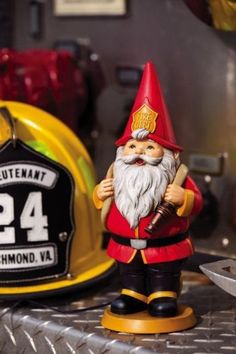 """10"""" Firefighter Gnome in Red and Black Uniform Outdoor Patio Garden Statue by Evergreen. $29.99. Firefighter Gnome in Red and Black Uniform StatueItem #842756Features a gnome in a fireman's uniform holding a water hoseDimensions: 10""""H x 4""""W x 4""""DMaterial(s): resin. Save 14% Off!"""