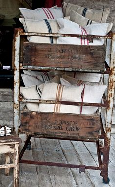 Vintage metal bakers rack with vintage fruit boxes and grain sack pillows