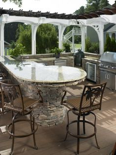 Outdoor kitchen with granite counter tops, bar, grill and natural stone.
