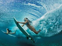 Picture of surfers underneath the waves in Oahu, Hawaii..navigating the crushing waves to get shots like this one of best friends Ha'a Keaulana, at right, and Maili Makana diving under a wave on their way to a surfing spot.
