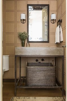 Clad in Phillip Jeffries Rivet Wallpaper, this beautifully styled powder room is fitted with a metal washstand holding a woven basket beneath a concrete countertop.