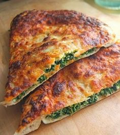 Spinach-Ricotta Calzone ~ What's a calzone? Simply put, it's pizza crust wrapped around its topping, rather than supporting it from beneath. You know how, when eating a slice of thin-crust pizza, you fold it in half so it doesn't droop and the cheese and tomato sauce stay put? A calzone is thin-crust pizza folded before you bake it — rather than after!