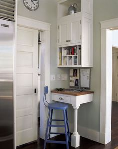 Fantastic kitchen with corner message station featuring white upper cabinets with pigeon holes over a white corner desk with polished nickel hardware and butcher block countertop. A blue metal bar stool lines the workstation beside a pocket slide door next to the stainless steel fridge.