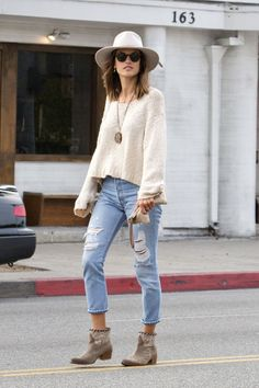 Channeling the laid-back California spirit, Alessandra Ambrosio goes casual in ripped denim, a loose cropped sweater with a hat to match, and western Zadig & Voltaire boots.