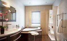 carrelage mural beige pastel en 3D, meuble de rangement en bois foncé et tablier de baignoire d'angle assorti