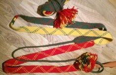Lagda kvinnoskoband låduga, i tre fält rött-gult-grönt tsavága, med zik-zak, viŋoga, mönster. Gällivare. Handarbete av Eva Simma. Braided saami shoelaces for women from Gällivare.