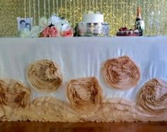 Fancy wedding Rosette tablecloths with these gorgeous floor length rosette tablecloth. It will add a touch of luxury and romance to your wedding or event! It will leave unforgettable impression for sweetheart tables and wedding cake tables. Available in many colors and sizes. Round or rectangular. We offer a discount on large quantity and accept custom orders. Please contact the shop directly for custom inquiry.  Materials: Satin and Taffeta  Color: Variable.  *THIS PICTURE IS AN ORIGINAL…