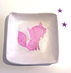 A carefully handmade trinket dish which has been made with air dry clay. The dish has been carefully imprinted with cute pink fox design.  The design also comes in other colours other than pink. Please see my other dishes for an idea of the colours available.  It is approximately 7cm in diameter, has been sealed, and then glossed with a high quality varnish.