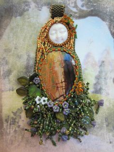 This pendant includes a particularly nice Cherry Creek jasper cabochon, a carved bone face, and glass beads, beaded on UltraSuede. It is about 2 inches wide by 5 inches tall including the bail and fringe.