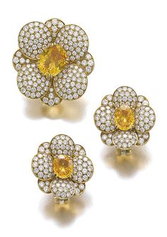 COLOURED SAPPHIRE AND DIAMOND DEMI-PARURE, VAN CLEEF & ARPELS Comprising: a clip/brooch of floral design centring on an oval sapphire of orangy-yellow tint, the petals pavé-set with brilliant-cut diamonds; and a pair of ear clips en suite; each signed Van Cleef & Arpels, numbered, French assay and maker's marks.