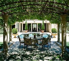 Poolside Pergola. Positioned by the pool and with sunlight filtering through its vine-clad roof arches, this pergola is a comfortable dining venue even on the hottest summer days. The metal in the overhead structure has a lighter look than wood and is echoed in the wrought-iron dining set.
