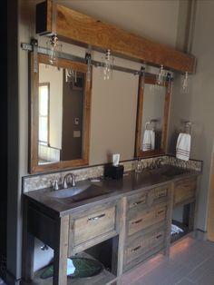 Concrete sinks, suspended beam lighting, barn door medicine cabinets, rock backsplash