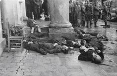 Zhytomyr Ukraine, summer 1941. Civilians lie dead in the street, possibly victims of a pogrom instigated by the German occupiers. Note the smiling faces of at least two Germans standing in the background and admiring the scene of death.