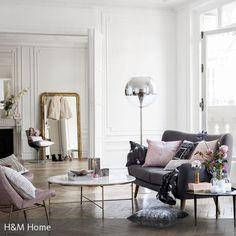 Die Räumlichkeit mit den Zierleisten auf den hohen weißen Wänden wirkt im Arrangement mit den rosafarbenen Sofakissen, dem Sessel und der kugelförmigen…