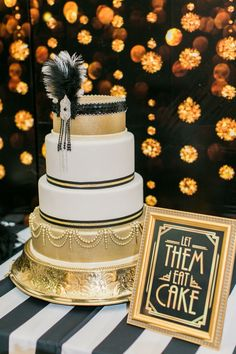 Great Gatsby Party. White and gold cake in a gold stand with black accents. Let them eat cake sign in an Art Deco style with a black and gold backdrop is the perfect combination.