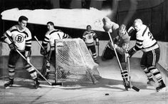 Blackhawks' rookie whiz Bobby Hull (16) swings behind the Boston net in pursuit of the puck during the Hawks' 2-1 victory over the Bruins at Chicago Stadium on Oct. 22, 1957. Bruin defender Larry Hillman, right, attempts to shove Hull out of play, while Boston's Allan Stanley waits for a possible pass out by Hull. Bruin goalie Don Simmons, who had just blocked a shot, glances over his shoulder at the flying young Hawk.