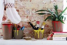 Bild av målade krukor som används till målarpenslar och pennor, med krukväxter, böcker och en kortlek på en vit hylla mot en tegelvägg.