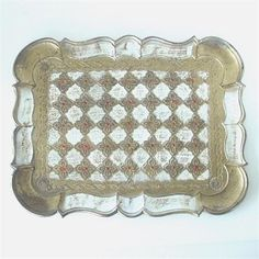 A pretty Mid Century vintage vanity tray in a Renaissance style quatrefoil pattern, withan antiqued gold and white finishwith dark red accents. It is 9 x 12with a scalloped edge, and made of a heavy and sturdy plastic. It is in excellent condition with no damage. Marked on the reverse Made in Italy.    Vintagepottery, glass, ephemera, buttons, jewelry and more are listed separately.