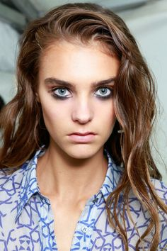 """Topshop Unique Spring 2014 RTW  """"We want her to look like she has just woken up on a beach somewhere—maybe Ibiza—after partying all night,"""" Murray explained. """"Her makeup, applied the night before, is sultry and even a little decayed."""" A brown gloss was painted over lids and a metallic silver pencil (also out for spring) was sketched into the inner corners of the eyes to play with textures."""