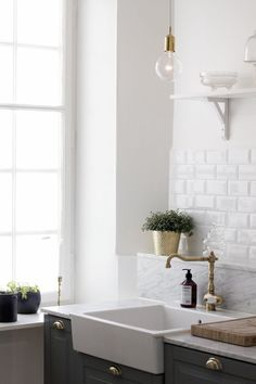 Light-filled kitchen in bare-bones white with tall ceilings, brick walls, and apron sink.