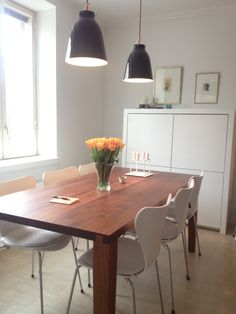 Dinig area with Arne Jacobsen chairs and Caravaggio lamps.