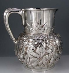 "A large ornate sterling silver Tiffany pitcher chased with roses and rose leaves against a finely stippled background. The pitcher weighs 32 troy ounces and measures 8 1/4"" tall. Circa 1880."