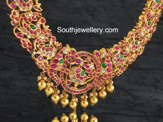 22 carat gold antique finish broad peacock design necklace studded with kundan from Navrathan Jewellers. For inquiries contact: info@navrathan.com Phone: +91 (080) 40913169/68 ADDRESS: 87, 1st Floor, MG Road, Bangalore. Related PostsUnique Peacock Guttapusalu NecklaceAntique Gundla Mala with Peacock Side PendantsKundan Peacock Necklace with Lakshmi PendantNakshi Work Mango Peacock NecklaceGraceful Peacock Kundan NecklaceNakshi Work peacock