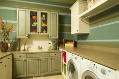 Green laundry room with traditional cabinets. This shows how to integrate the taller counters for the machines with a regular counter.