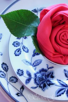 Hot Pink Rosette Napkins were featured on a StoneGable tablescape this earlier this week. They added a big punch of color and a little extra surprise to my Mikasa Indigo Bloom Tablescape…      My e-mail has been burstingwith so many request for a rosettenapkin folding tutorial!  …
